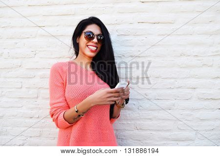 Young beautiful latin woman texting on her phone. Woman using a cellphone wearing casual clothes.