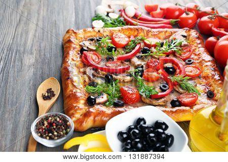 Freshly homemade pizza on wooden background