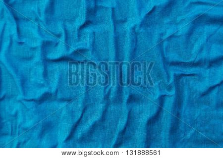 Bright blue wrinkled linen fabric, abstract background with copy space