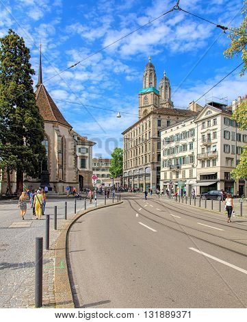 Zurich, Switzerland - 26 May, 2016: view along the Limmatquai quay with the towers of the Grossmunster cathedral in the background. Zurich is the largest city in Switzerland and the capital of the Swiss canton of Zurich.
