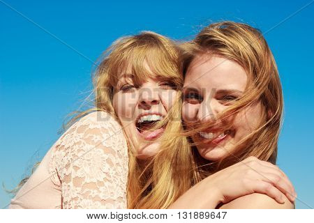 Two young women best friends blonde cheerful girls having fun outdoor against blue sky wind blowing in hair. Summer happiness friendship concept.