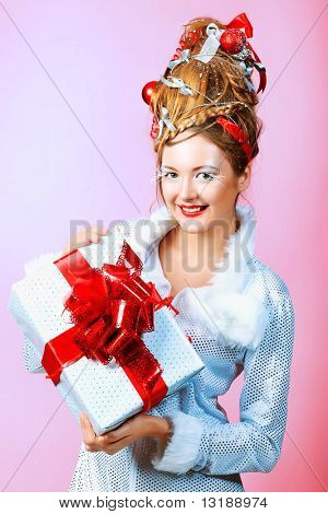 Beautiful young woman in Santa Claus clothes holding a present over pink background.