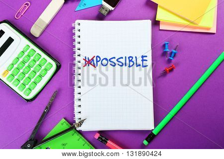 Word impossible transformed into possible on notebook page with school supplies