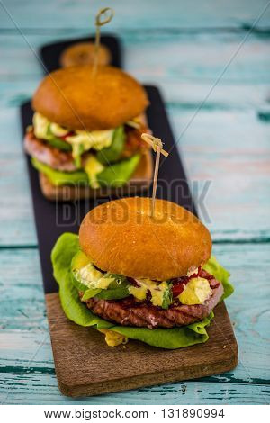 Tasty grilled tuna burger with lettuce and mayonnaise served on wooden table with copyspace