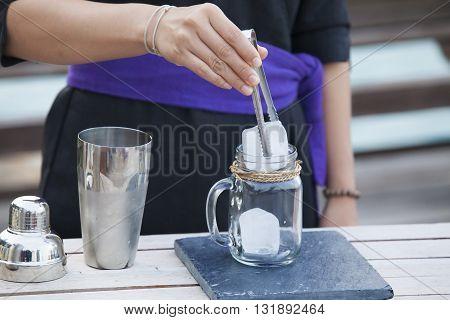 Bartender is stirring cocktails on bar counter toned image