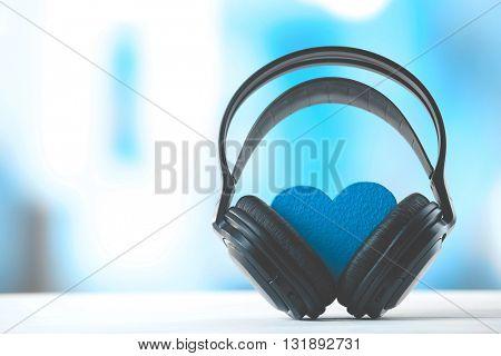 Black headphones with heart on unfocused background