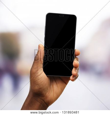 Hand shows mobile smart phone, urban city blurred background