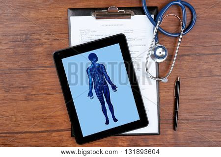 Medical picture on the tablet screen and stethoscope on wooden background