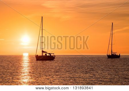 Yachts in the sea at sunset, Yachting. Romantic trip on luxury yacht during the sea sunset.