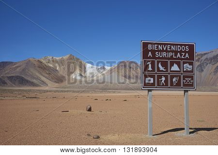 Colourful mountains, and sign, at Suriplaza on the Altiplano of north east Chile.