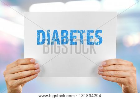 Male hands holding sheet of paper with text diabetes on blurred background