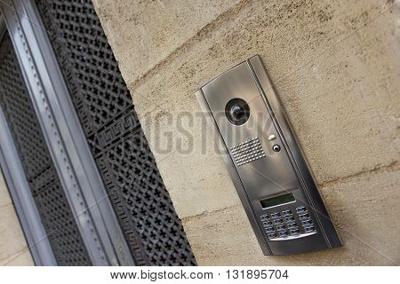 Close up of a modern intercom on a stone facade of a French house