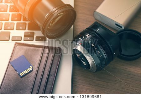 Photographer table , camera lens, sd cards, portable power bank, laptop on table.