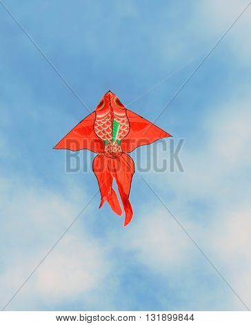 Flying red kite in form of fish against the blue sky with clouds
