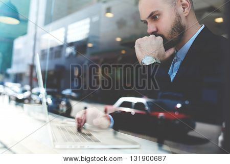 View through the window of confident pensive businessman is monitoring the shares on the stock market via portable net-book while is sitting in urban coffee shop of New York city. Double exposition