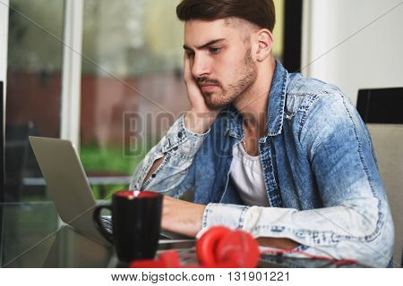 Young handsome man studying with his laptop headphones and coffee. Indoor.