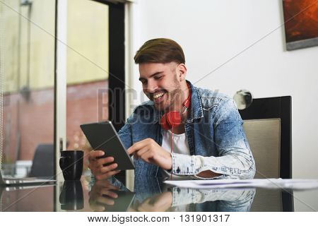 Young handsome man studying with his tablet headphones and coffee. Indoor.