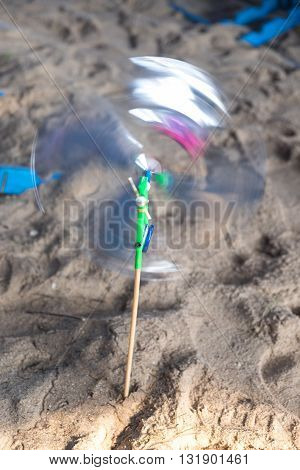 moving pinwheel on beach close-up, toy hand make