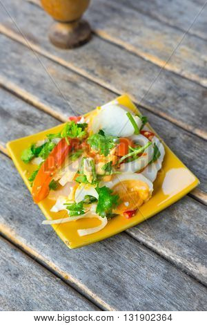 salted eggs salad on yellow dish in wood table