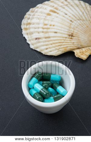 Jar with heap of blue green round capsule pills with medicine antibiotic