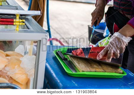 Woman Selling Watermelonwatermelon cut with a knife