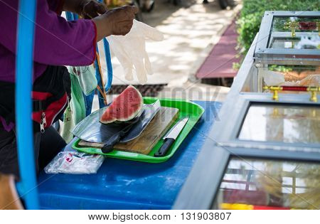 Costermonger Selling Watermelonwatermelon cut with a knife