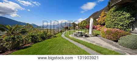 Beautiful garden of a villa, stone benches and table