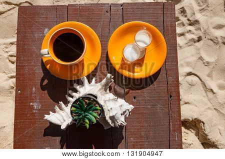 Hot black coffee serve with milk and sugar in orange cup and plate on a wooden table with succulent and sea shell at the beach front cafe