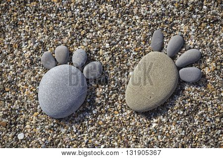 Two trace feet made of a pebble stone on the beach backdrop. Close up
