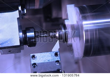 cutting and drilling of metal parts processing on lathe in workshop. Selective focus on tool