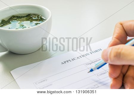 Hand with pen over application form with tea cup