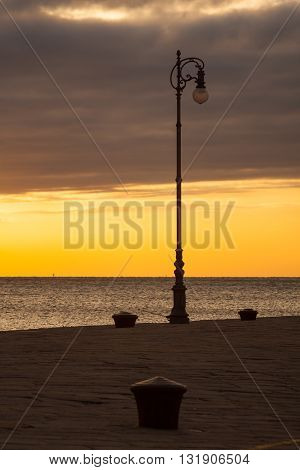 Street lamp at sunset next to the Trieste sea