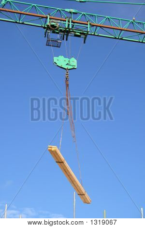 Close Up Of A Crane Lifting Planks Of Wood.
