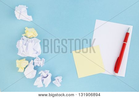 Creative process - crumpled and wrinkled paper wads with fresh sheet of blank paper