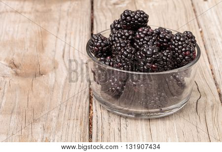 Clear glass bowl of ripe blackberries on a rustic farm picnic table in summer.