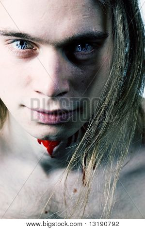 Young man with blue eye lens and blood on his throat