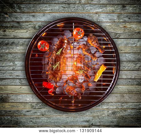 Pork ribs, chicken legs and vegetable served on grill, wooden planks as background
