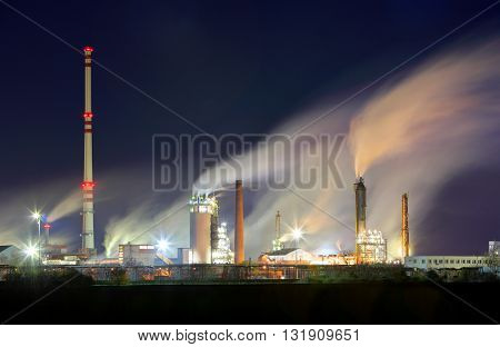 Oil refinery industry plant with smokestack at night