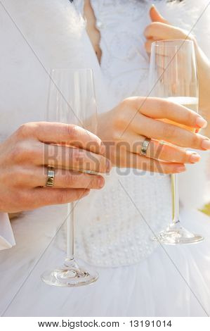 Two hands with wedding rings holding champagne glasses