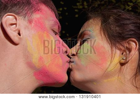 Kiss. Portrait of happy couple in love on holi color festival