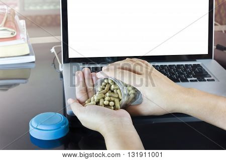 Hand And Moringa Capsules With Blank Screen Notebook Or Computer On Black Counter Background, Pill O