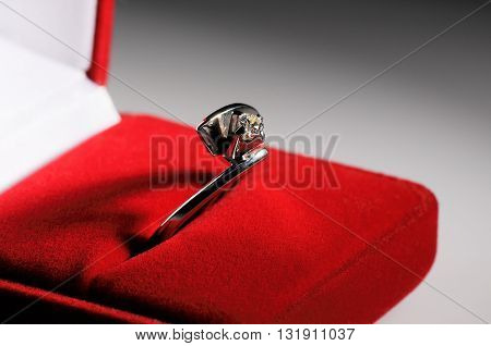 Silver finger ring with precious stone in red box over blurry gray background selective focus