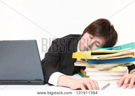 portrait of businessman Sleeping on the desk on white background