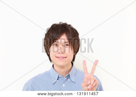 portrait of young Japanese man showing a victory sign on white background