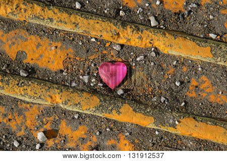 Pink heart on yellow tactile paving slab