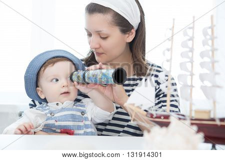 Happy Kid And Mom Playing With Toy Sailing Boat Indoors.