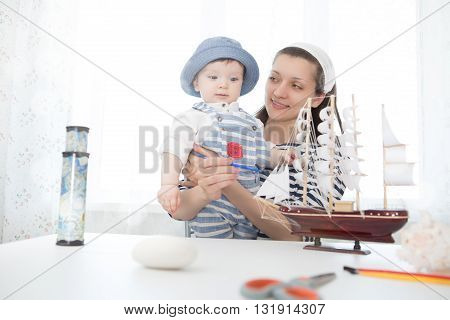 Mother And Her Child Boy Making Model Ship.