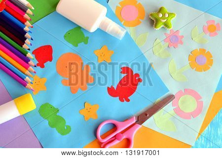 Paper octopus, fish, starfish, crab, flowers. Project idea using a colored paper. Applique work for children. Crafts from colored paper. Glue, scissors, pencils, eraser. Funny background