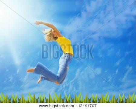 Beautiful blonde girl jumps over green grass