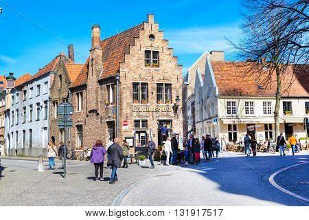 Bruges, Belgium - April 10, 2016: Street view with medieval traditional houses, people in popular belgian destination Brugge, Belguim